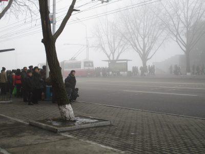 霧が出ている平壌でバスを待つ人々